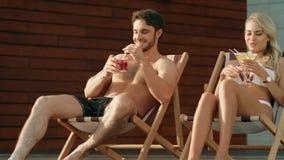 Cócteles de consumición de los pares del verano en sillas del sol Mujer atractiva que se relaja en bikini almacen de metraje de vídeo