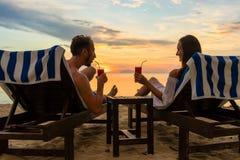 Cócteles de consumición de los pares jovenes en una playa en la puesta del sol durante vacaciones imagen de archivo