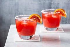 Cócteles de los Margaritas de la naranja de sangre con hielo y el borde salado imagen de archivo libre de regalías