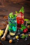 Cócteles de restauración con la menta, la cal, el hielo, las bayas y el carambola en el fondo de madera Bebidas de la vitamina Co Imagenes de archivo