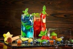 Cócteles de restauración del verano con la menta, la cal, el hielo, las bayas y el carambola en el fondo de madera Dos bebidas du Fotos de archivo libres de regalías