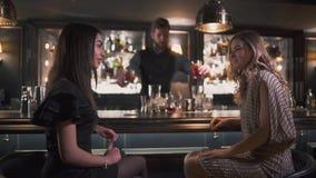 Cócteles de servicio del camarero a las muchachas bonitas mientras que sea de charla y sonriente en la buena barra moderna almacen de metraje de vídeo