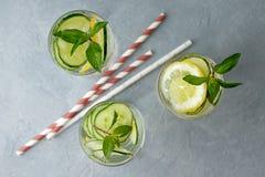 Cócteles del refresco con el pepino, el limón y la menta en fondo gris Fotografía de archivo libre de regalías