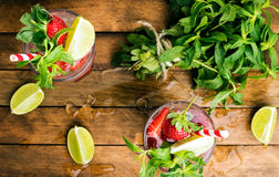 Cócteles del verano del mojito de la fresa con la menta y la cal en vidrios Foto de archivo libre de regalías