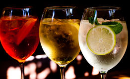 Cócteles: el aperol spritz, sprizz (spriss), royale de Martini (fondo oscuro) Vino espumoso Champán Foto de archivo libre de regalías