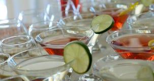 Cócteles rojos de Martini en vidrios en una barra o un partido metrajes