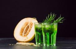 Cócteles verdes del alcohol Bebidas del frío y un melón en un fondo negro Bebidas con estragón, hielo y el melón dulce Copie el e Imagen de archivo libre de regalías