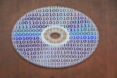 Código binário refletido em uma superfície de disco compacto na perspectiva de madeira um fundo fotos de stock