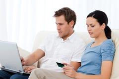 Código bonito da leitura da mulher em um cartão de crédito Imagens de Stock