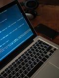 Código de ordenador en convertirse del web del ordenador portátil y el teléfono móvil imagen de archivo