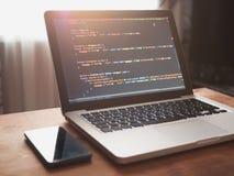 Código de ordenador en convertirse y el teléfono móvil del web del ordenador portátil fotografía de archivo libre de regalías