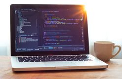 Código do PHP em tornar-se da Web do portátil e caneca branca na luz solar fotografia de stock royalty free
