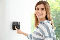 Código entrando da jovem mulher no keypa do sistema de alarme foto de stock