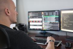 Código programado del hombre en la pantalla de ordenadores en el escritorio imagen de archivo