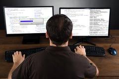 Código programado del hombre en los ordenadores imágenes de archivo libres de regalías