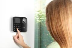 Código que entra de la mujer joven en telclado numérico del sistema de alarma imagenes de archivo