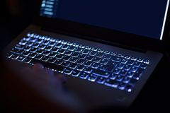 Código que mecanografía del pirata informático del programador o de ordenador en el teclado del ordenador portátil imágenes de archivo libres de regalías