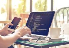 Códigos fonte de um programador fêmea e telefone celular de datilografia da utilização em uma cafetaria fotografia de stock royalty free