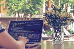 Códigos fuente que mecanografían de un programador de sexo femenino en un ambiente de trabajo relajante El estudiar, trabajando,  foto de archivo