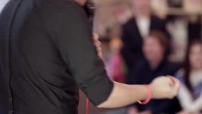 Cómico de pie de sexo masculino irreconocible con un micrófono delante de una audiencia almacen de metraje de vídeo
