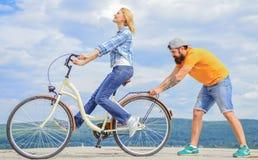Cómo aprender montar la bici como adulto Muchacha que completa un ciclo mientras que el novio la apoya Enseñe al adulto a montar  foto de archivo