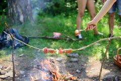 Cómo asar las salchichas con las verduras Salchichas en fondo de la hoguera del palillo Olor ahumado de la comida asada Roasty to foto de archivo