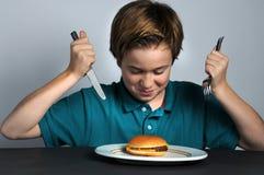 Cómo comer una hamburguesa Imagen de archivo libre de regalías