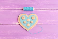 Cómo coser una decoración del corazón del fieltro step Únase a los bordes del fieltro del corazón del fieltro con el hilo azul Hi Foto de archivo
