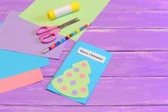 Cómo crear los artes simples de la tarjeta de Navidad para los niños preceptoral El papel coloreado junta las piezas, las tijeras Imágenes de archivo libres de regalías