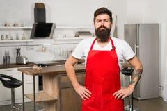 Cómo dar vuelta a cocinar en casa en hábito Soporte rojo del delantal del inconformista barbudo del hombre en cocina Tienda de mu imagen de archivo