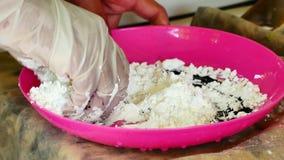 Cómo hacer coloreó el polvo, festival del holi Las manos salando colorante alimentario se están mezclando con el almidón de maíz  almacen de metraje de vídeo