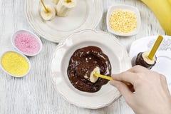 Cómo hacer el chocolate sumergió plátanos - paso a paso, tutorial Foto de archivo