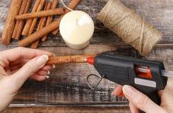 Cómo hacer la vela adornada con los palillos de canela preceptoral Imágenes de archivo libres de regalías