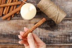 Cómo hacer la vela adornada con los palillos de canela preceptoral Imagen de archivo
