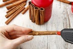 Cómo hacer la vela adornada con los palillos de canela - tutorial Fotos de archivo libres de regalías