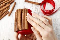 Cómo hacer la vela adornada con los palillos de canela - tutorial Imagen de archivo libre de regalías