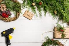 Cómo hacer que la Navidad la puerta enrruella el proceso de trabajo El lugar de trabajo del ` s del decorador Visión superior foto de archivo