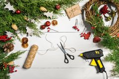 Cómo hacer que la Navidad la puerta enrruella el proceso de trabajo El lugar de trabajo del ` s del decorador Visión superior fotografía de archivo