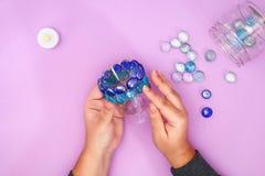Cómo hacer su propia palmatoria del vidrio innecesario o de los guijarros plásticos y de cristal Paso a paso Decoración del inter foto de archivo