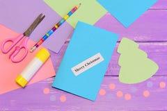 Cómo hacer tarjeta de felicitación Feliz Navidad step Sistema del papel coloreado, tijeras, lápiz, palillo del pegamento, árbol d Imagen de archivo libre de regalías