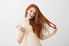 Cómo sobre la música que escucha hacer día perfecto Mujer joven feliz satisfecha del pelirrojo, celebrando smartphone y llevar Fotografía de archivo