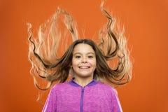 Cómo tratar el pelo rizado Peinado agradable y ordenado Extremidades fáciles que hacen el peinado para los niños Pelo largo del p imagen de archivo libre de regalías