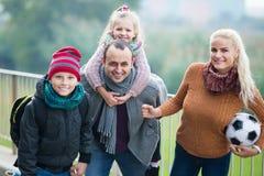 Cónyuges con los niños que presentan en parque del otoño Foto de archivo libre de regalías