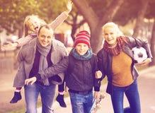 Cónyuges con los niños que presentan en parque del otoño Imágenes de archivo libres de regalías