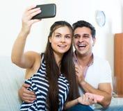 Cónyuges jovenes positivos que plantean y que hacen el selfie Fotografía de archivo