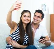 Cónyuges jovenes positivos que plantean y que hacen el selfie Fotografía de archivo libre de regalías
