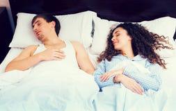 Cónyuges jovenes que duermen firmemente en cama Fotos de archivo