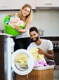 Cónyuges mezclados que hacen el lavadero regular Imágenes de archivo libres de regalías