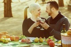Cónyuges que beben el vino en la tabla Fotos de archivo libres de regalías