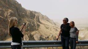 Córka bierze fotografię telefonem komórkowym jej starsi rodzice na urlopowej wycieczce w górach przy drogową przerwą szczęśliwa r zbiory